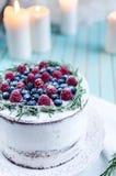 O bolo caseiro decorou bagas na placa sobre o fundo de madeira de turquesa Imagem de Stock Royalty Free