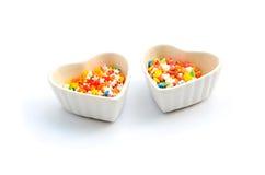 O bolo colorido do coração e da estrela fundo do branco polvilha e do copo Foto de Stock