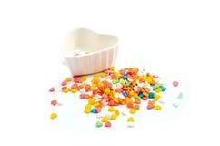 O bolo colorido do coração polvilha e copo no fundo branco Foto de Stock Royalty Free