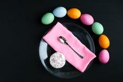O bolo da Páscoa e os ovos coloridos em uma tabela preta Imagens de Stock Royalty Free