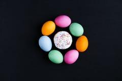 O bolo da Páscoa e os ovos coloridos em uma tabela preta Imagem de Stock