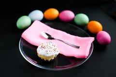 O bolo da Páscoa e os ovos coloridos em uma tabela preta Fotografia de Stock