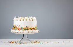 O bolo de aniversário branco de Buttercream com polvilha imagens de stock royalty free