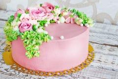 O bolo de aniversário com flores aumentou no fundo branco Imagens de Stock Royalty Free