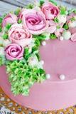 O bolo de aniversário com flores aumentou no fundo branco Imagens de Stock