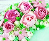 O bolo de aniversário com flores aumentou no fundo branco Fotos de Stock
