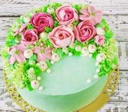 O bolo de aniversário com flores aumentou no fundo branco Fotografia de Stock