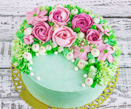 O bolo de aniversário com flores aumentou no fundo branco Foto de Stock Royalty Free