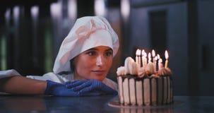 O bolo de aniversário com velas para dentro em um padeiro atrativo bonito da senhora da cozinha da padaria veio ao bolo e ao sorr filme