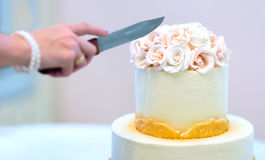 O bolo de casamento festivo com flores, flores amarelo-alaranjadas, beliche, bonito, delicado, a noiva corta o bolo imagens de stock royalty free