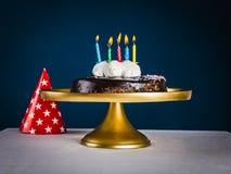 O bolo de chocolate com cinco velas e o vermelho coloriram o tampão do cone com s fotos de stock