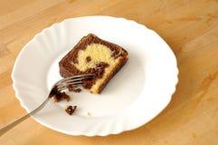 O bolo de mármore de Chololate em uma placa mordiscou com uma forquilha Fotos de Stock Royalty Free