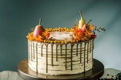 O bolo de mel derrama sobre o chocolate e decorado com peras e espinheiro cerval de mar em uma tabela de madeira Do outono vida d Imagem de Stock