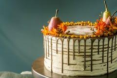 O bolo de mel derrama sobre o chocolate e decorado com peras e espinheiro cerval de mar em uma tabela de madeira Do outono vida d Fotografia de Stock Royalty Free