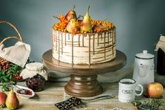 O bolo de mel derrama sobre o chocolate e decorado com peras e espinheiro cerval de mar em uma tabela de madeira Do outono vida d Fotos de Stock