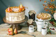 O bolo de mel derrama sobre o chocolate e decorado com peras e espinheiro cerval de mar em uma tabela de madeira Do outono vida d Fotografia de Stock