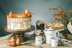 O bolo de mel derrama sobre o chocolate e decorado com peras e espinheiro cerval de mar em uma tabela de madeira Do outono vida d Foto de Stock Royalty Free
