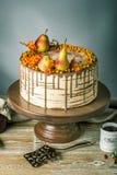 O bolo de mel derrama sobre o chocolate e decorado com peras e espinheiro cerval de mar em uma tabela de madeira Do outono vida d Imagens de Stock Royalty Free