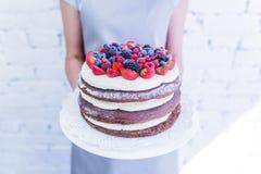 O bolo do whoopie do chocolate na placa com bagas frescas, ` s das mulheres entrega guardar Imagens de Stock