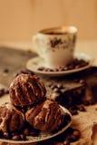 O bolo doce com uma cereja e os feijões de café no fundo da xícara de café e aquecem o lenço feito malha Fundo saboroso do alimen Foto de Stock