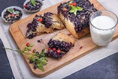 O bolo e os queques da baga com mirtilos e morangos em uma placa verde e em uma mesa de madeira serviram com leite e e Imagem de Stock