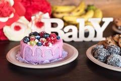 O bolo e os queques de aniversário com cumprimento de madeira assinam no fundo escuro De madeira cante com os doces do bebê e do  Fotos de Stock Royalty Free