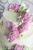 O bolo festivo do casamento com creme floresce o lilás no fundo branco Imagem de Stock
