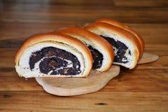 O bolo fresco corado cortado com sementes de papoila encontra-se na placa de corte de madeira na superfície de madeira fotos de stock