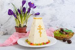 O bolo tradicional da Páscoa do coalho com frutos cristalizados e ovos de chocolate, mola floresce o açafrão no fundo da luz do f Fotos de Stock