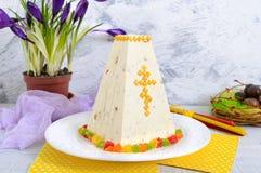O bolo tradicional da Páscoa do coalho com frutos cristalizados e ovos de chocolate, mola floresce o açafrão no fundo da luz do f Imagens de Stock Royalty Free