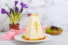O bolo tradicional da Páscoa do coalho com frutos cristalizados e ovos de chocolate, mola floresce o açafrão no fundo da luz do f Fotografia de Stock Royalty Free