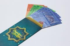 O bolso do dinheiro ? dado do adulto ?s crian?as durante a celebra??o de Eid Mubarak em Mal?sia fotografia de stock royalty free