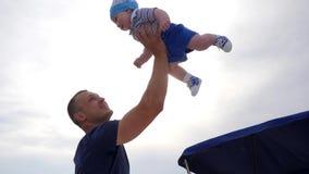 O bom jogo do paizinho com filho fora, paizinho aumentou o bebê nos braços, criança nas mãos fortes do ` s do pai na luz solar, video estoque