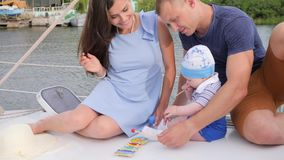 O bom pai com mãe toma do filho no barco de prazer, paizinho e a mamã com criança pequena passa o tempo no iate, vídeos de arquivo