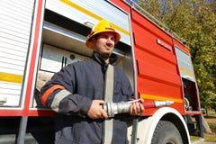 O bombeiro está na frente de um carro de bombeiros Imagem de Stock