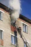 O bombeiro extingue o incêndio em um apartamento em prédio alto Foto de Stock Royalty Free
