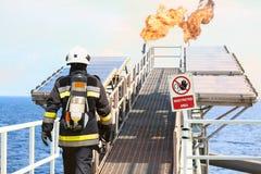 O bombeiro na indústria de petróleo e gás, o sapador-bombeiro bem sucedido no trabalho, o terno do fogo para o lutador com fogo e Foto de Stock