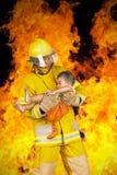 O bombeiro salvou a criança do fogo Imagem de Stock Royalty Free