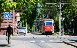 O bonde atravessa uma aleia verde na cidade de Tomsk Fotografia de Stock Royalty Free