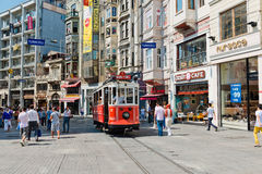 O bonde retro move-se ao longo de uma rua ocupada de Istiklal em Istambul Foto de Stock