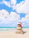 O boneco de neve arenoso de sorriso no chapéu vermelho de Santa no mar encalha fotografia de stock