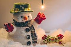 O boneco de neve e a ampola estão entre a pilha da neve na noite, no Feliz Natal e na noite silenciosos do ano novo feliz Imagens de Stock