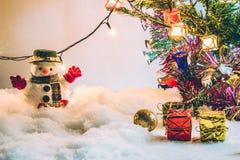 O boneco de neve e a ampola estão entre a pilha da neve na noite silenciosa, iluminam acima o hopefulness e a felicidade no Feliz Imagem de Stock