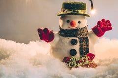 O boneco de neve e a ampola estão entre a pilha da neve na noite silenciosa, iluminam acima o hopefulness e a felicidade no Feliz Fotografia de Stock
