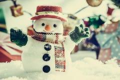 O boneco de neve e a ampola estão entre a pilha da neve na noite silenciosa, iluminam acima o hopefulness e a felicidade no Feliz Fotos de Stock