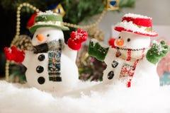 O boneco de neve e a ampola estão entre a pilha da neve na noite silenciosa, iluminam acima o hopefulness e a felicidade no Feliz Fotografia de Stock Royalty Free