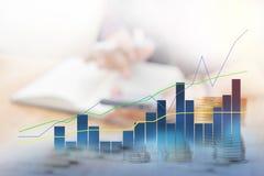 O borrão do fundo de um homem de negócios senta o trabalho O primeiro plano é gráficos, estatísticas indica o sentido positivo fotografia de stock royalty free