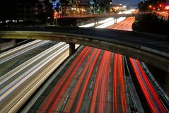 O borrão dos sinais no crepúsculo e das pontes que cruzam-se sobre a autoestrada 110 imagem de stock