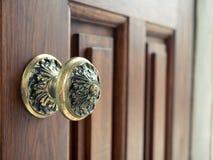 O botão de porta do vintage na madeira vermelha lustrou a porta foto de stock