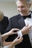 O botão de punho do marido da asseguração da mulher foto de stock